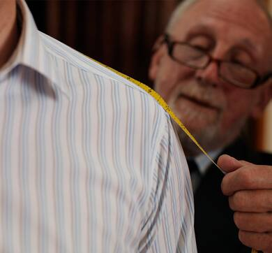 Tailor taking shirt measurements