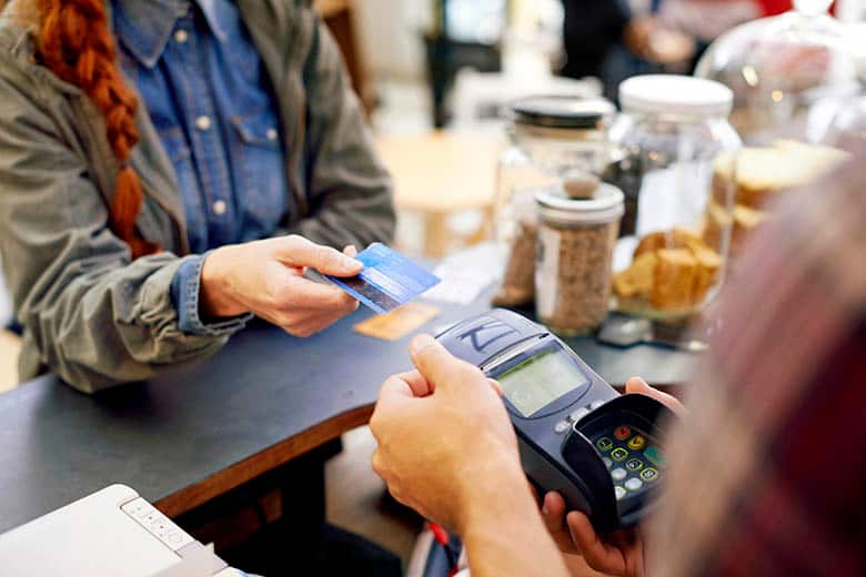 Shot of a customer paying for their order with a debit machine in a cafe.
