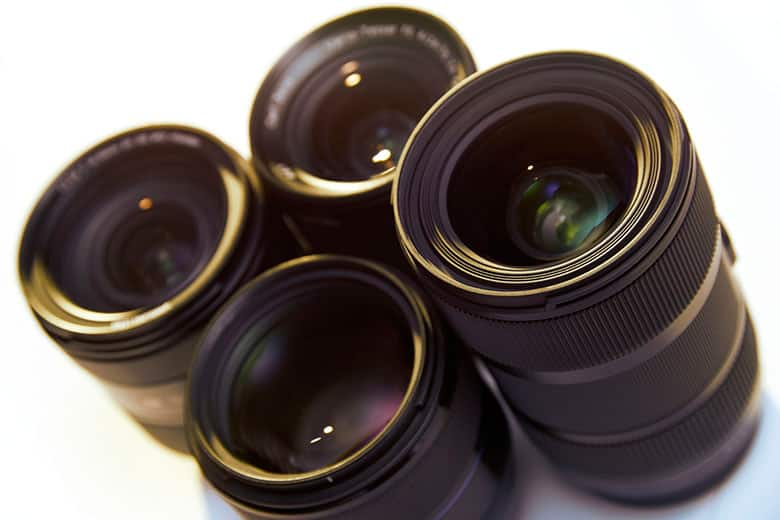 Still life shot of group of photographic lenses isolated on white background, with warm backlight and flare. High angle view