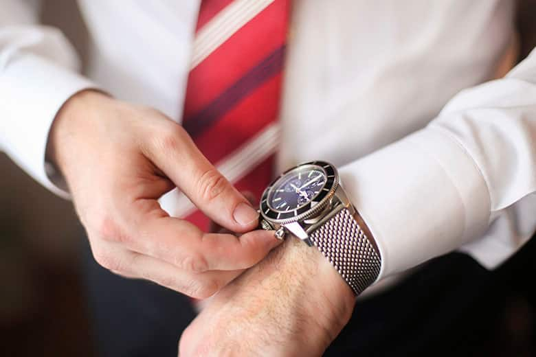 Unrecognizable male business person winding up an expensive hand watch.